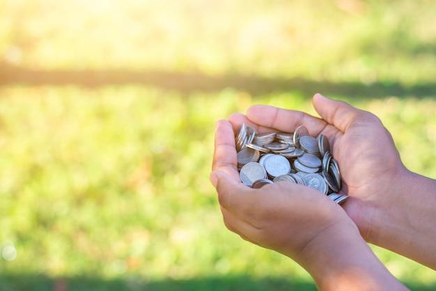 Spaar geldconcept met het muntstuk van de handholding op groene aardachtergrond