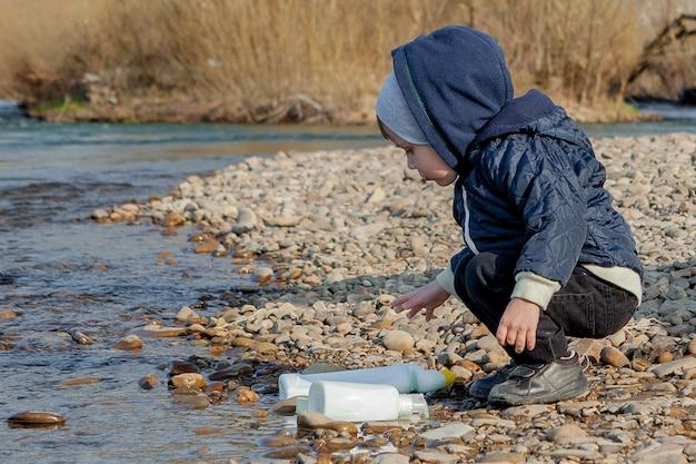 Spaar milieuconcept, een kleine jongen die afval en plastic flessen op het strand verzamelt om het afval te dumpen.