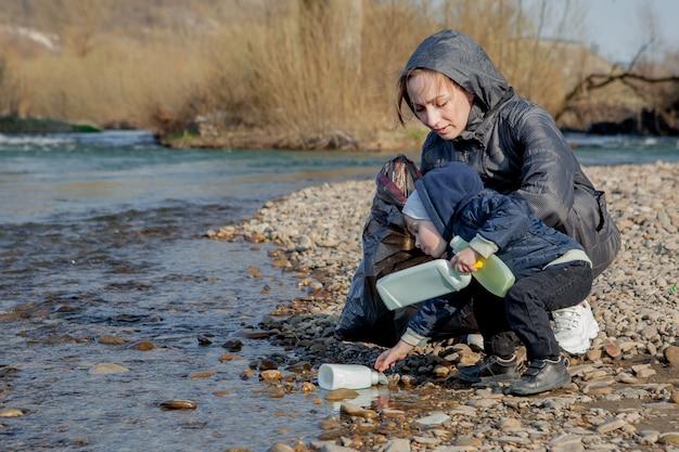 Spaar milieuconcept, een kleine jongen en zijn moeder verzamelen afval en plastic flessen op het strand om in het afval te dumpen.