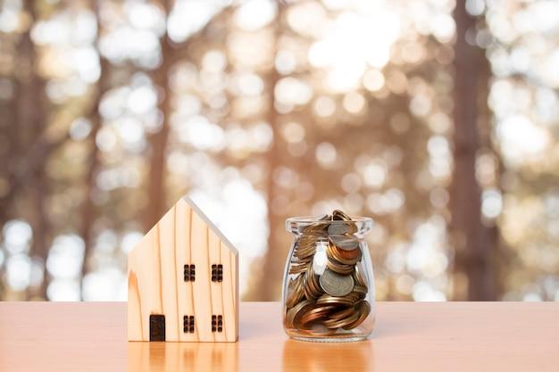 Spaargeld in een potglas met een houten huismodel.