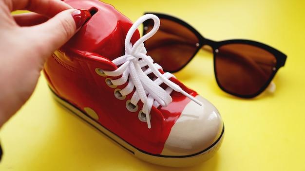Spaarpot in de vorm van sneakers. zonnebril op een gele achtergrond. het concept van besparingen op vakantie en zomervakantie. geld besparen