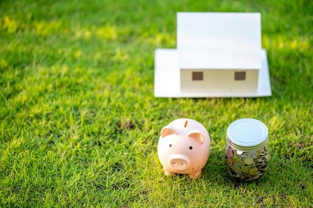 Spaarvarken en een huismodel, concept geld besparen voor huis en onroerend goed.