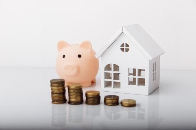 Spaarvarken en huismodel met muntjes. besparingen concept.