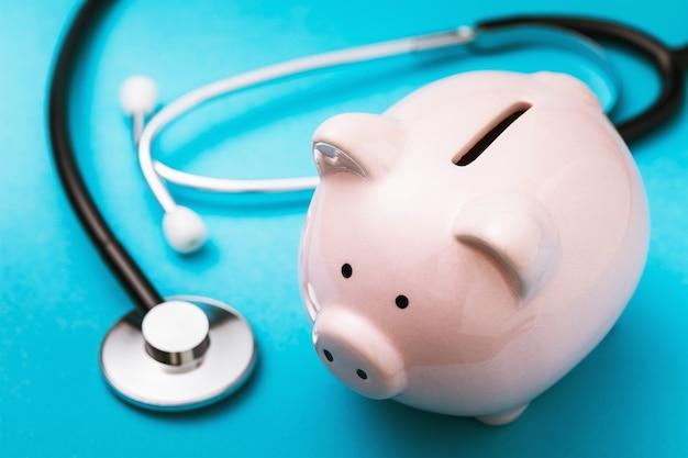 Spaarvarken en medische stethoscoop op een blauwe oppervlakte