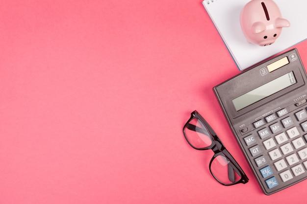 Spaarvarken en rekenmachine op kleur, bovenaanzicht,