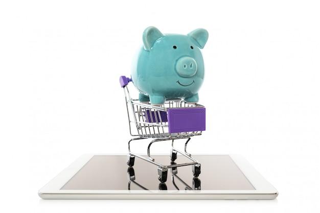 Spaarvarken in karretje boodschappenwagentje op witte achtergrond concept van besparingen online winkelend