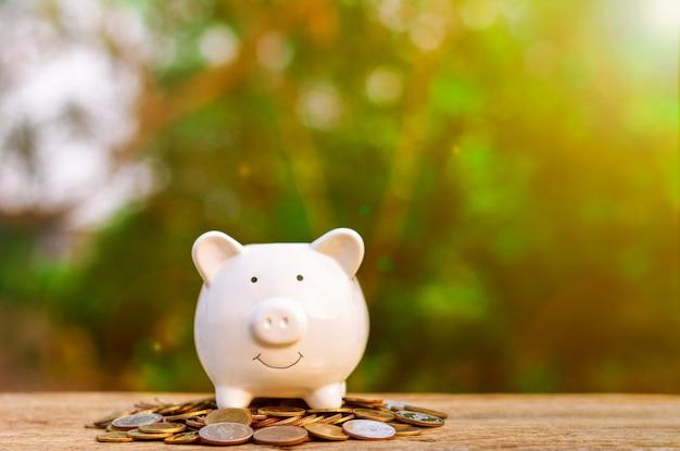 Spaarvarken meer dan stapel van gouden munten op oude houten lijst