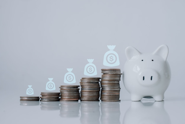 Spaarvarken met geld munt stapel positieve inkomensgroei op de witte houten vloer. investeren, economisch, pensioen met kopieerruimte, bannerformaat, groeigrafiek.