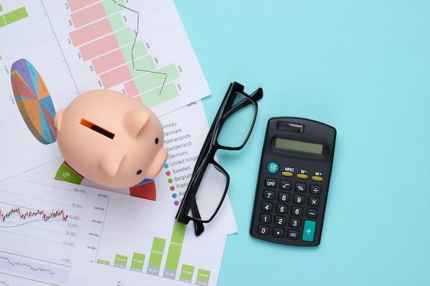 Spaarvarken met grafieken en diagrammen, rekenmachine, bril op een blauw. economische analyse, kosten, statistieken