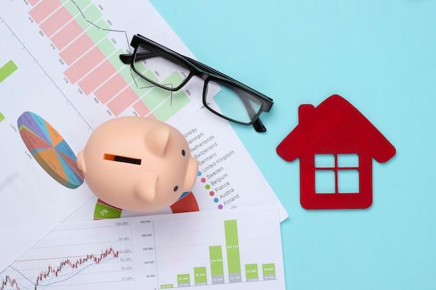 Spaarvarken met grafieken en grafieken, huiscijfer op blauw. huisvestingskostenanalyse