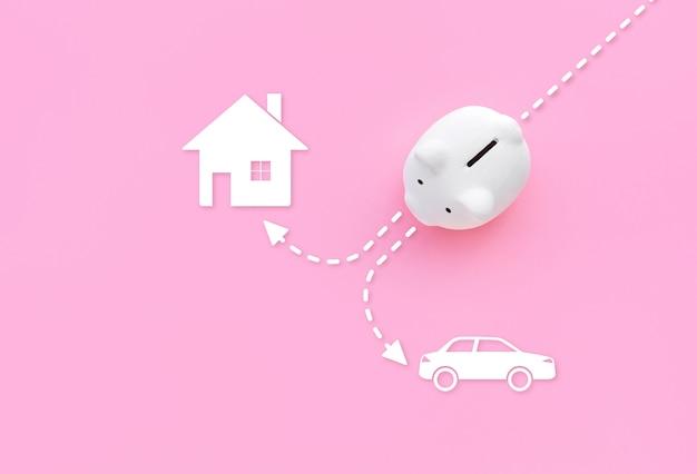Spaarvarken met huis en auto pictogram op roze pastel kleur achtergrond