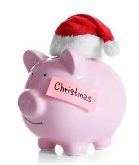 Spaarvarken met kerstmuts op wit wordt geïsoleerd
