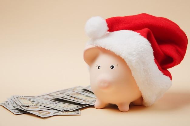 Spaarvarken met kerstmuts stelletje dollars bankbiljetten contant geld geïsoleerd op beige achtergrond. geld accumulatie investeringen, bankdiensten, rijkdom concept. kopieer ruimte reclame mock-up.