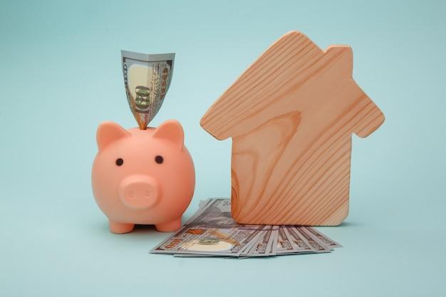Spaarvarken met model van huis en geldbankbiljetten op blauwe achtergrond. spaargeld voor huis kopen