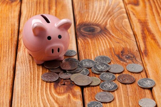 Spaarvarken met munt op houten tafel