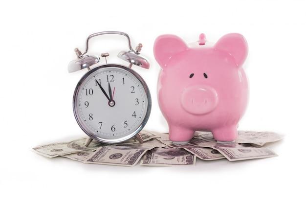 Spaarvarken naast wekker op dollars