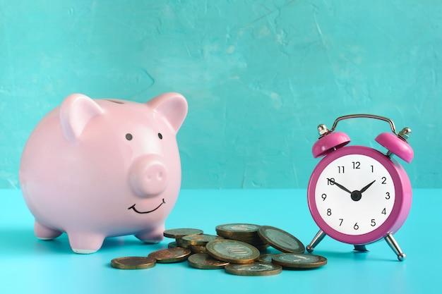 Spaarvarken op blauw. bij een stapel munten en een roze wekker.