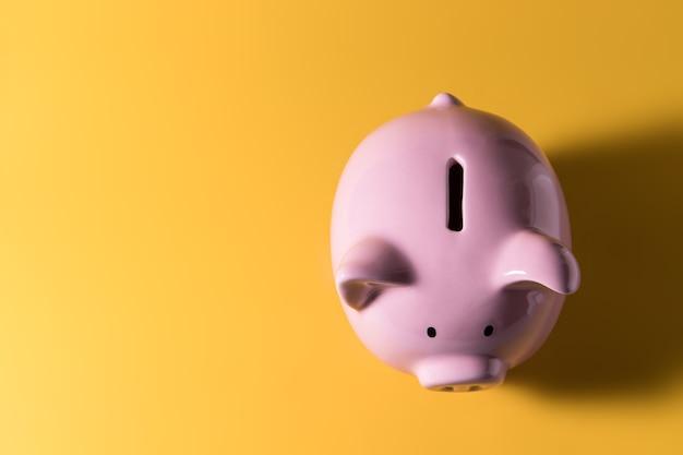 Spaarvarken op gele achtergrond voor economie, geldrijkdom en financieel concept besparen
