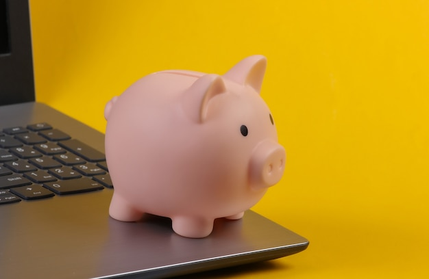 Spaarvarken op laptop toetsenbord. geel oppervlak. verdien geld online of via internet