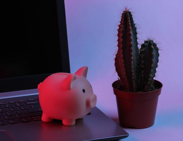 Spaarvarken op laptop toetsenbord met cactus. neon gradiënt rood-blauw, ultraviolet licht. verdien geld online of via internet