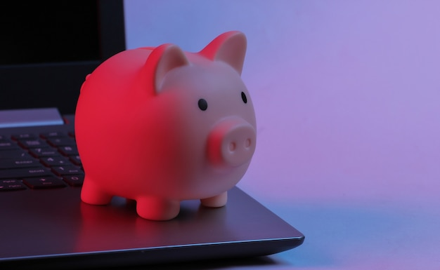Spaarvarken op laptop toetsenbord. neon gradiënt rood-blauw, ultraviolet licht. verdien geld online of via internet