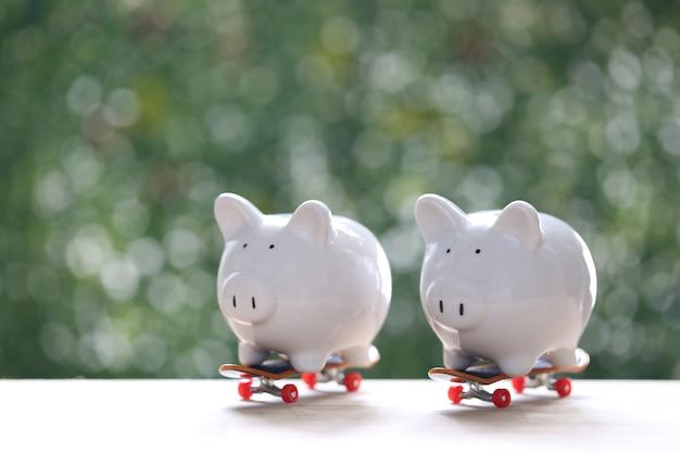 Spaarvarken op skateboard met natuurlijke groene achtergrond, bedrijfsinvesteringen en onroerende goederenconcept