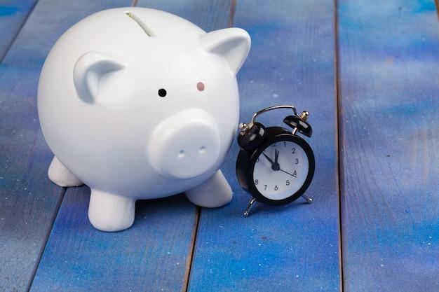 Spaarvarken sparen munt en wekker, tijd en geld.