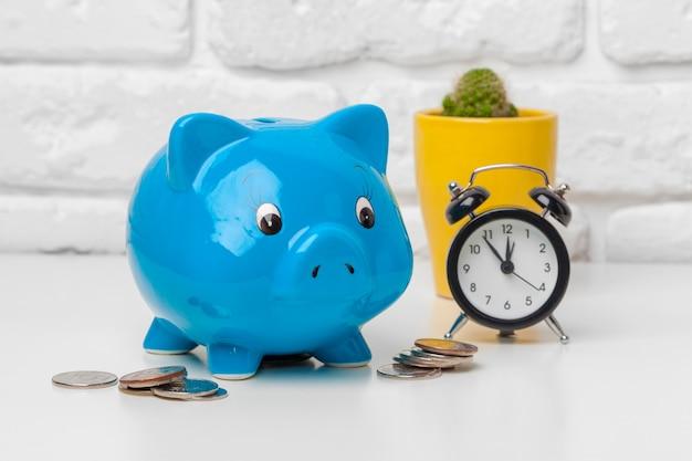 Spaarvarken sparen munt en wekker, tijd en geldconcept.