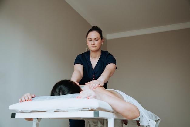 Spabehandelinggezondheidszorgconcept massagetherapeut die massage doet