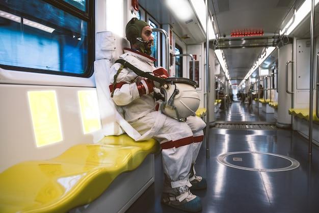 Spaceman in een futuristisch station. man met ruimtepak vertrekt naar zijn werk en haalt de trein