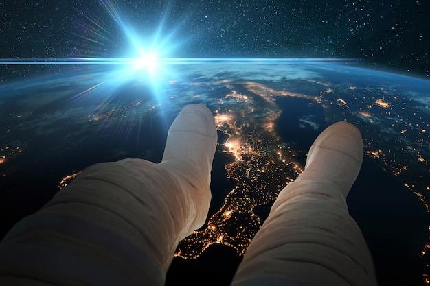 Spaceman zit en kijkt naar de blauwe planeet aarde met nachtverlichting van steden vanuit de ruimte. astronautenvoeten op de achtergrond van de aarde bij blauwe zonsondergang. kosmos behang. man rust in een baan bij zonsopgang