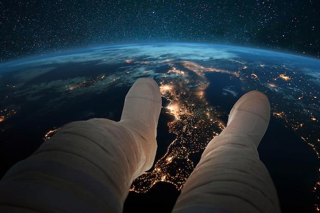 Spaceman zit en kijkt naar de blauwe planeet aarde met nachtverlichting van steden vanuit de ruimte. astronautenvoeten op de achtergrond van de aarde. kosmos behang. man rust in een baan