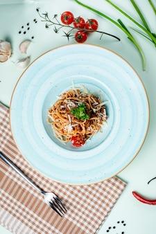 Spaghetti bolognese gegarneerd met kaas en kruiden