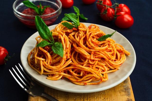 Spaghetti bolognese in een plaat op blauw