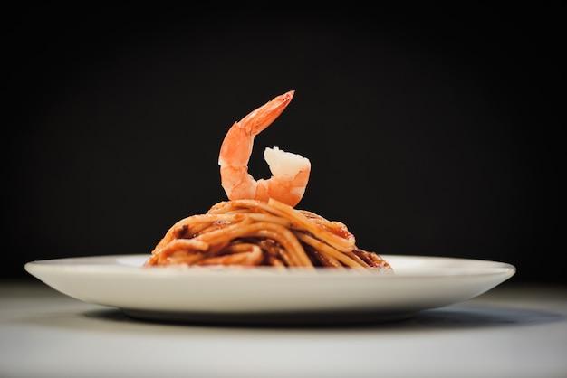 Spaghetti bolognese italiaanse deegwaren met garnalengarnaal die op witte plaat met zwarte worden gediend