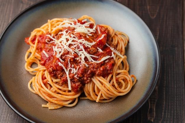 Spaghetti bolognese saus of tomatensaus op een donkere houten bord