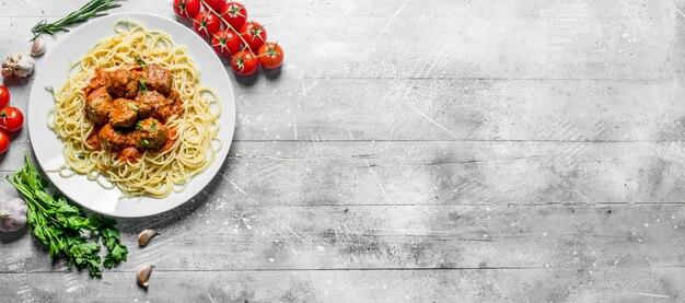Spaghetti en gehaktballen met peterselie en tomaten. op witte houten achtergrond