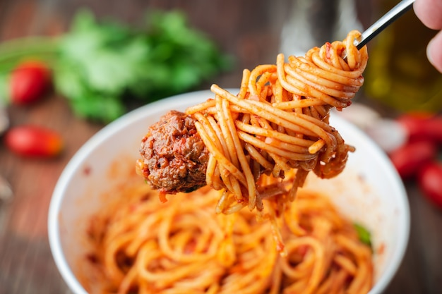 Spaghetti en gehaktballen met tomatensaus in witte kom op houten rustieke bord