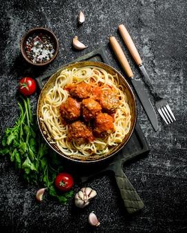 Spaghetti en vleesballetjes in pan met kruiden, kruiden en tomaten. op rustieke achtergrond