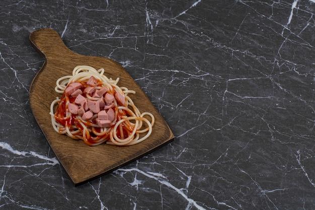 Spaghetti en worstjes met saus op houten snijplank.