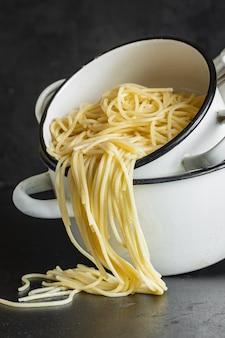 Spaghetti gekookt in een pan italiaanse durumtarwe gerecht biologisch, gezond gerecht op tafel