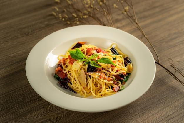 Spaghetti gekruid spek met basilicumbladeren.