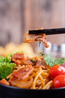 Spaghetti in een zwarte kop met tomaten en sla.