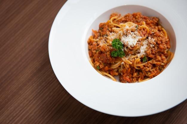Spaghetti in tomatensaus, geserveerd op een bord, peterselie in een witte schotel, op een bruine houten vloer, italiaans eten