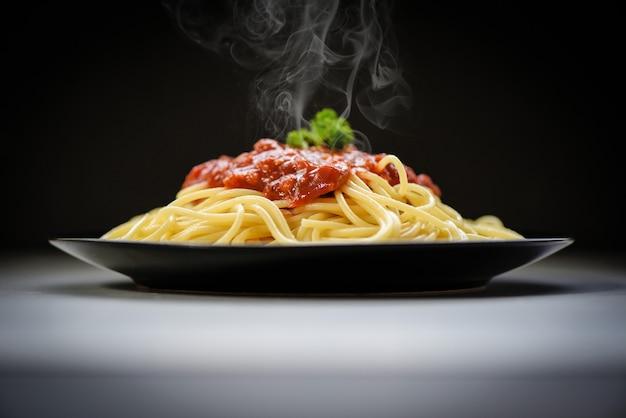 Spaghetti italiaanse deegwaren die op zwarte plaat met tomatensaus en peterselie in het restaurant italiaanse voedsel en menuconcept worden gediend. spaghetti bolognese op zwart