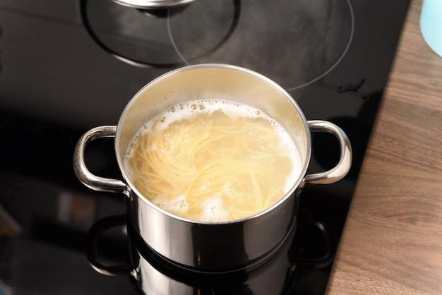 Spaghetti koken in een pan op het elektrische fornuis.