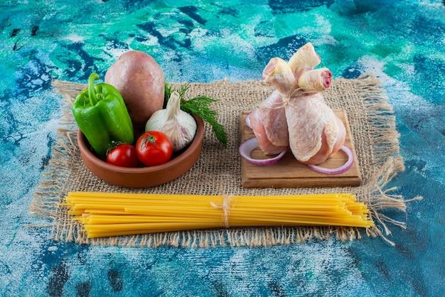 Spaghetti, kom met groenten naast drumsticks op een bord op jute, op de blauwe achtergrond.