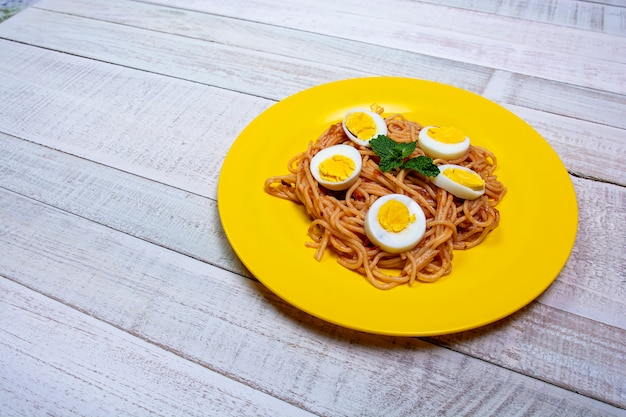 Spaghetti maaltijd, tomatensaus, munt op houten tafel. close-up bekijken