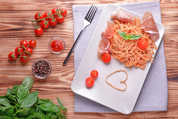 Spaghetti met amatricianasaus en spek op houten tafel, bovenaanzicht
