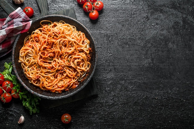 Spaghetti met bolognesesaus in pan met servet, tomaten en knoflook
